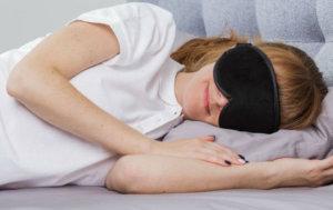Девушка спит в маске