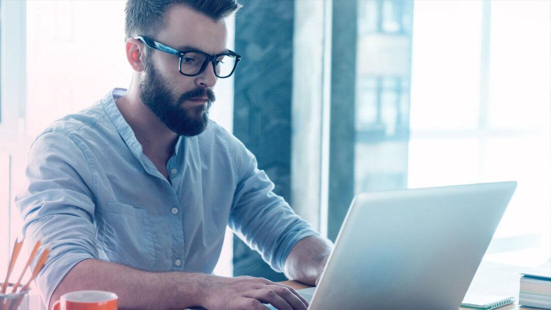 Мужчина в очках за ноутбуком