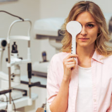 Young beautiful woman at the ophthalmologist on consultation, covering one eye and checking her visual acuity